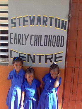 little girls stand under school sign