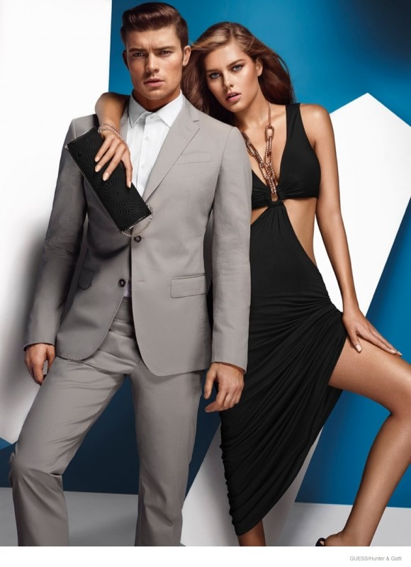 The Guess by Marciano woman wears a cut-out black dress to match her man's grey suiting attire