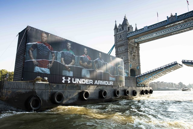 Under Armour shipping containers full of new Armour baselayer product pass under Tower Bridge on their way down the River Thames