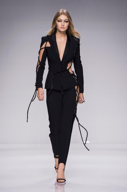 Gigi Hadid walks Atelier Versace's spring 2016 show wearing a black pantsuit with cut-out details