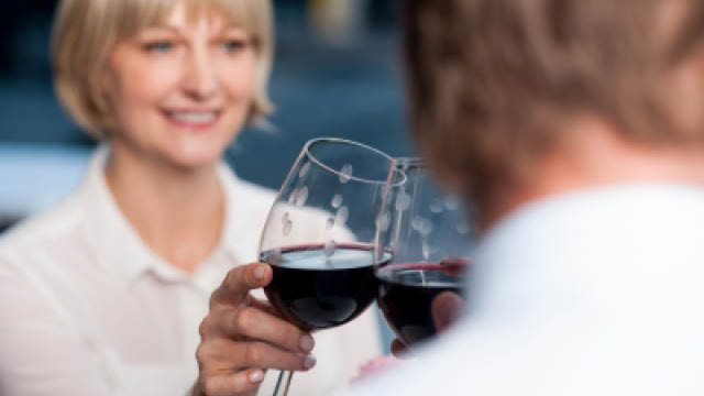 Attractive couple raises a glass of red wine in cafe.