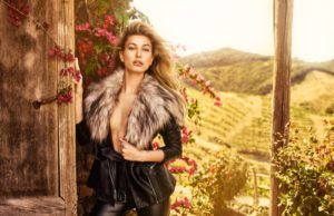 Hailey Baldwin models faux fur adorned jacket with black pants from Guess