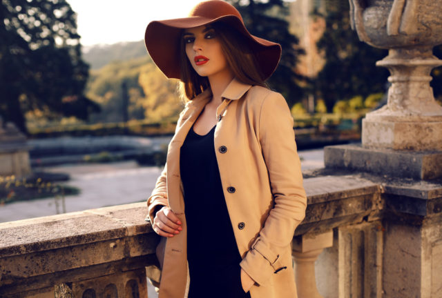 fashion outdoor photo of beautiful ladylike woman with dark straight hair wearing elegant coat and felt hat,posing in autumn park