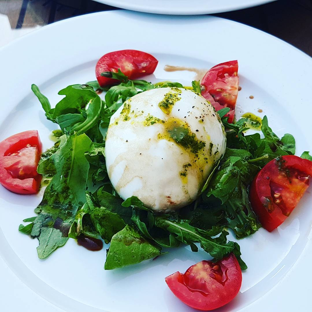 Burrata di bufala. Burrata with tomato, wild rocket & basil dressing