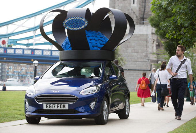 Brand new 2017 Ford Fiesta (Mk VII), given a regal makeover by royal milliner Rosie Olivia, travels over Tower Bridge in London adorned with crown of Fiesta parts celebrating the car's track record as UK's favourite car since 2008