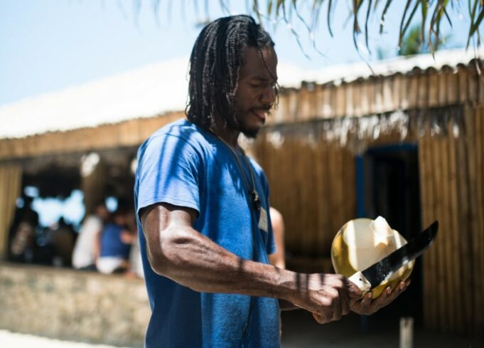 man peeling coconut in Jamaica