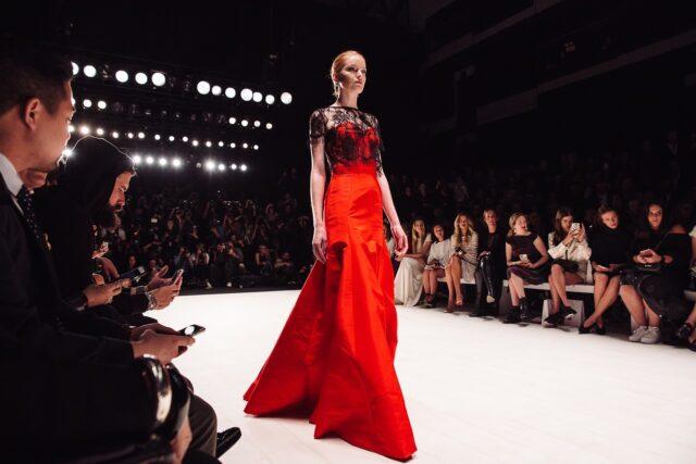 Women walking down the a catwalk in a red evening dress