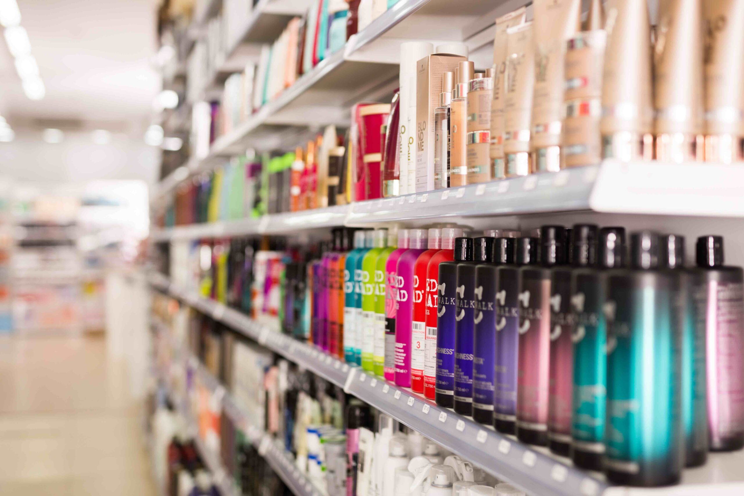 Plastic bottles of various hair care products on store shelves