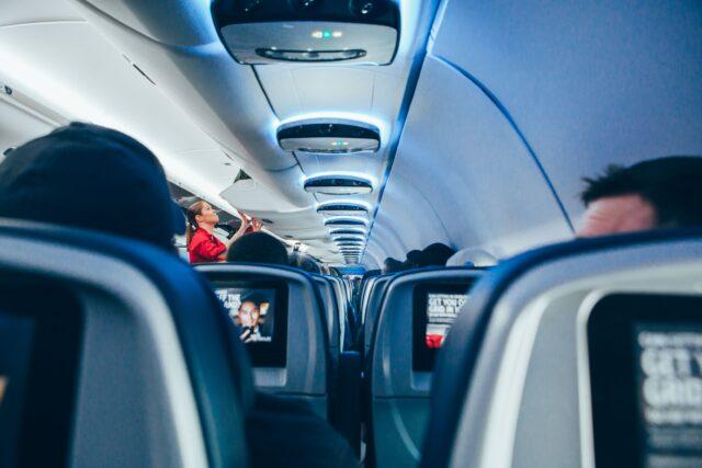 flight attendant packing bags in the overhead locker