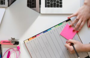 Woman writing on a pink post it note